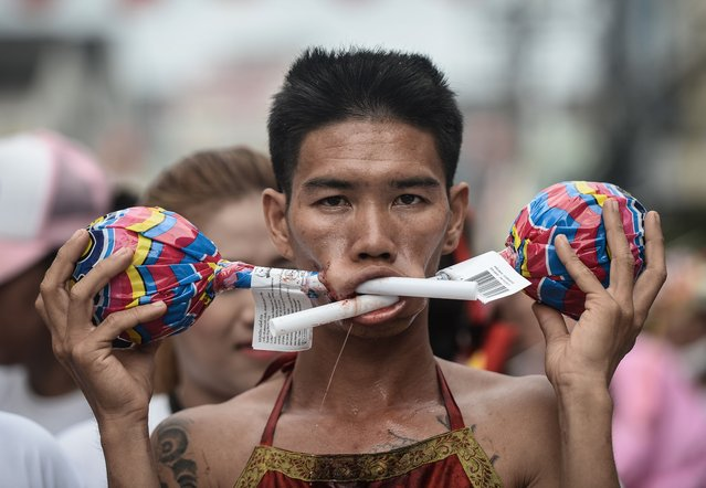 A devotee of the Nine Emperor Gods parades through the town of Phuket with giant lollipops pierced through his cheeks during the annual Phuket Vegetarian Festival in the southern province of Phuket on October 3, 2016. (Photo by Lillian Suwanrumpha/AFP Photo)