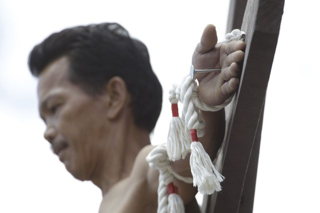 A Filipino penitent is nailed to the cross during Good Friday rituals Friday, March 29, 2013 in Cutud, Pampanga province, northern Philippines. Several Filipino devotees had themselves nailed to crosses Friday to remember Jesus Christ's suffering and death, an annual rite rejected by church leaders in this predominantly Roman Catholic country. (Photo by Aaron Favila/AP Photo)