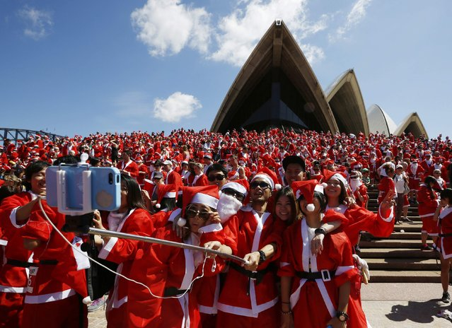 Runners in Father Christmas suits pose for a 'selfie' photo after completing an annual Santa fun run from Darling Harbour to the Sydney Opera House, December 7, 2014. (Photo by Jason Reed/Reuters)