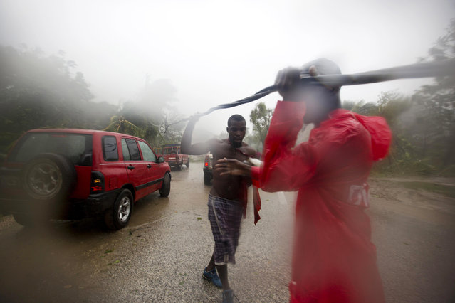 Two men remove a downed power line to allow vehicles passage, in Petit Goave, Haiti, Tuesday, October 4, 2016. Matthew slammed into Haiti's southwestern tip with howling, 145 mph winds Tuesday, tearing off roofs in the poor and largely rural area, uprooting trees and leaving rivers bloated and choked with debris. (Photo by Dieu Nalio Chery/AP Photo)