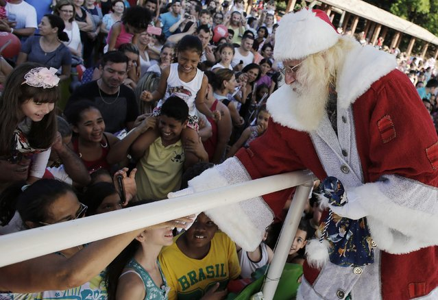 Vitor Martins, dressed as Santa, greets children in Sao Caetano do Sul's town square, near Sao Paulo, December 7, 2014. (Photo by Nacho Doce/Reuters)