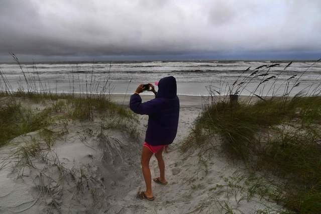 A local resident takes pictures on the beach with her dog ahead of hurricane Matthew in Jacksonville, Florida, on October 6, 2016. Some 1.5 million people are under evacuation orders in Florida in preparation for mighty Hurricane Matthew to make a direct hit on the state, the governor said Thursday. Matthew has already killed 27 people as it barreled its way through the Caribbean, with the Bahamas the last to be hit. (Photo by Jewel Samad/AFP Photo)