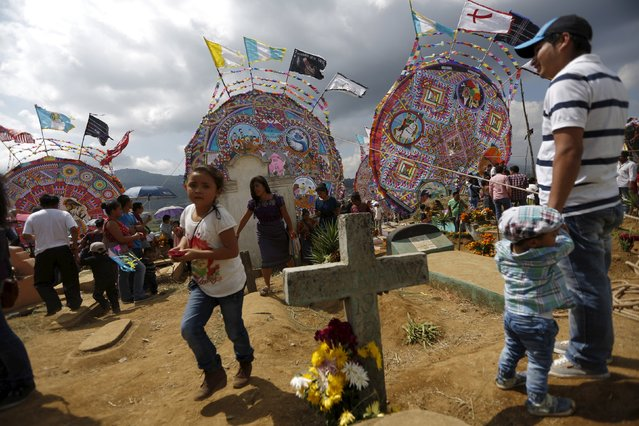 People stand in the middle of the graves and in front of giant kites in the cemetery of Santiago Sacatepequez, Guatemala, November 1, 2015. (Photo by Jorge Dan Lopez/Reuters)