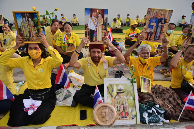 Royalist supporters hold up images of Thailand's King Maha Vajiralongkorn and Queen Suthida as they wait to catch a glimpse of him as he heads to the Grand Palace for a Buddhist ceremony for the late king Chulalongkorn in Bangkok on October 23, 2020. (Photo by  Lillian Suwanrumpha/AFP Photo)