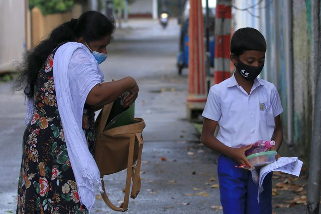 A Sri Lankan student  wearing a protective mask heads towards the exam center as his mother (L) checks his bag after handing over the admission papers and food near an examination center for Grade-5 scholarship exam at Colombo, Sri Lanka on 11 October 2020. (Photo by Tharaka Basnayaka/NurPhoto via Getty Images)
