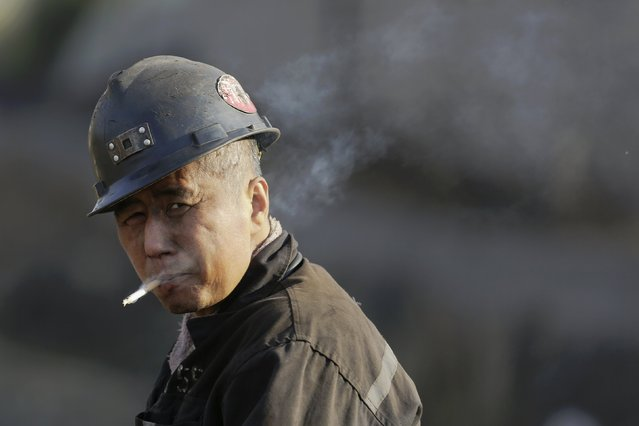A miner smokes after his work as he leaves a coal mine from the state-owned Longmay Group on the outskirts of Jixi, in Heilongjiang province, China, October 24, 2015. (Photo by Jason Lee/Reuters)