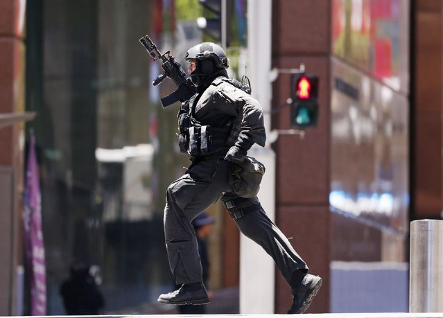 A police officer runs across Martin Place near Lindt cafe, where hostages are being held, in central Sydney December 15, 2014. Hostages were being held inside the central Sydney cafe where a black flag with white Arabic writing could be seen in the window, local television showed on Monday, raising fears of an attack linked to Islamic militants. (Photo by David Gray/Reuters)
