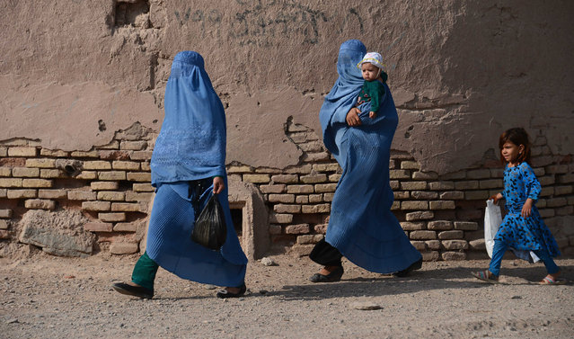 Afghan women walk with their children through the old quarters of Herat on September 20, 2016. (Photo by Aref Karimi/AFP Photo)