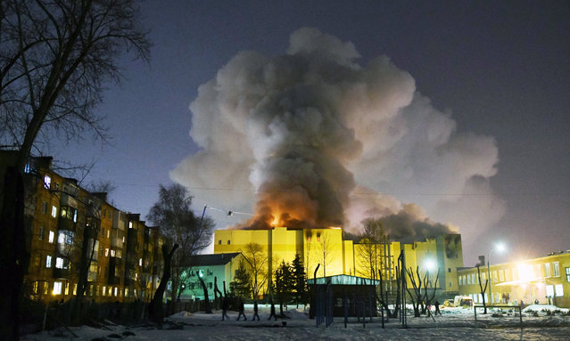 Smoke raises over a shopping center Zimnaya Vishnya in the West Siberian city of Kemerovo, Russia, early 26 March 2018. At least 56 people reportedly died, including many children and around 60 are still lost. (Photo by Alexander Patrin/EPA/EFE/A42.RU)