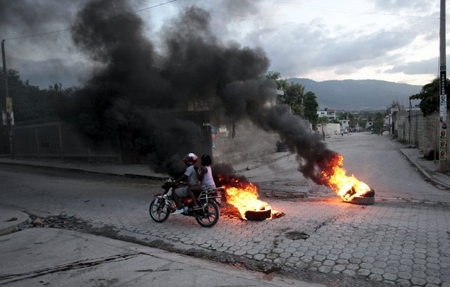 A motorbike passes burning tyres at a barricade during protests after the announcement of the results of the presidential election, on a street in Port-au-Prince, Haiti, November 5, 2015. Ruling party candidate Jovenel Moise led voting in Haiti's Oct. 25 presidential election with 32 percent, followed by former government executive Jude Celestin with 25 percent, according to official results announced on Thursday. (Photo by Andres Martinez Casares/Reuters)