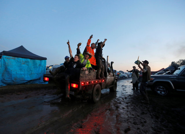 """Men ride on the back of a truck driving through mud on the final night of the Deni Ute Muster in Deniliquin, New South Wales, Australia, October 1, 2016. In the small rural town of Deniliquin, on the edge of Australia's vast outback, around 20,000 """"ute"""" lovers gathered in the mud to champion a national treasure deemed surplus to requirements by the big car manufacturers. Part car, part pickup truck, the Australian-made utility vehicle has become synonymous with farmers Down Under and is the centrepiece of the annual Deni Ute Muster festival, a two-day alcohol-fuelled celebration of all things rural Australia. Now in its 18th year, the festival has grown to include country music performances from Grammy award-winning artist Keith Urban, a rodeo, whip-cracking championship and gallery of artwork created with chainsaws. (Photo by Jason Reed/Reuters)"""