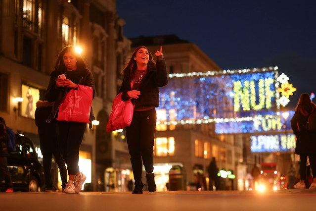 Pedestrians illuminated by Christmas lights walk through Oxford Street amid the coronavirus disease (COVID-19) outbreak in London, Britain, November 19, 2020. (Photo by Simon Dawson/Reuters)