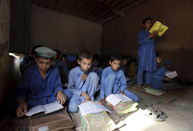 A boy reads from a book while attending a class at a school in Kababiyan refugee camp in Peshawar, Pakistan, October 6, 2015. (Photo by Faisal Mahmood/Reuters)