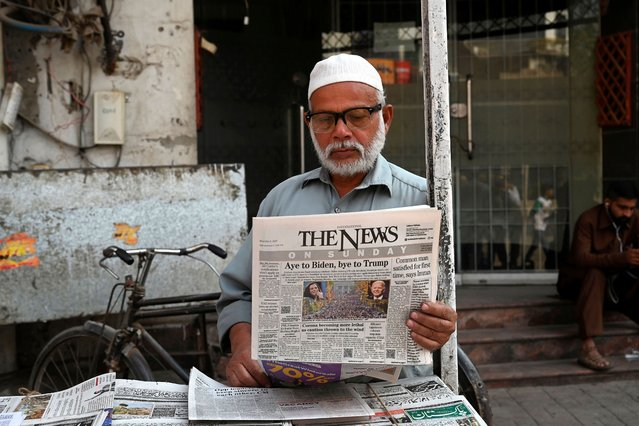 A man reads a morning newspaper showing a photograph of newly elected US President Joe Biden, at a newspaper stall in Lahore on November 8, 2020. (Photo by Arif Ali/AFP Photo)