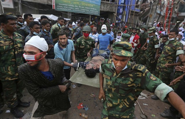 A garment worker, one of more than 40 found alive on Friday, is rushed from the scene on a stretcher. (Photo by Kevin Frayer/Associated Press)