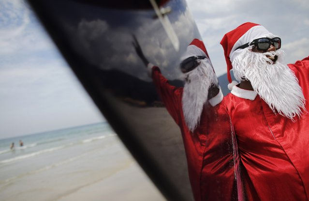 Carlos Bahia, dressed as Santa Claus, waves to people at the Maresias beach, in the state of Sao Paulo December 9, 2014. (Photo by Nacho Doce/Reuters)