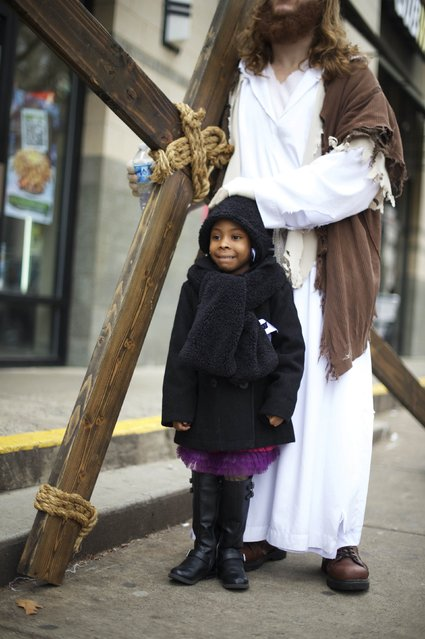 "Casey Green, 4, poses with Michael Grant, 28, ""Philly Jesus"", in a break from his carrying a 12 foot cross 8 miles through North Philadelphia to LOVE Park in Center City as part of a Christmas walk to spread the true message of the holiday in Philadelphia, Pennsylvania December 20, 2014. (Photo by Mark Makela/Reuters)"