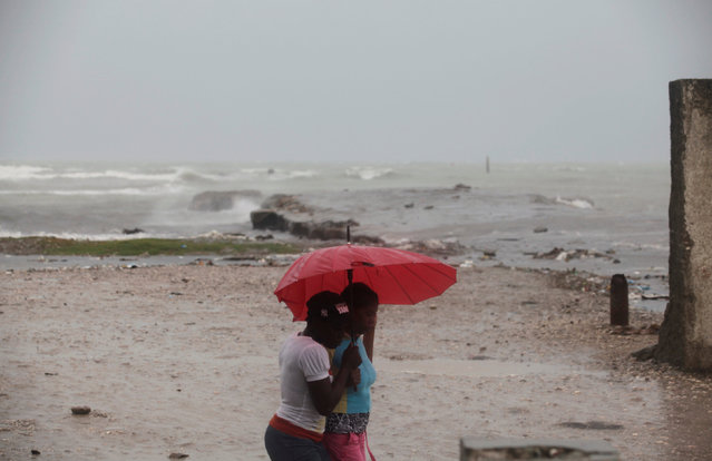 Two women protect themselves from rain with an umbrella ahead of Hurricane Matthew in Les Cayes, Haiti, October 3, 2016. (Photo by Andres Martinez Casares/Reuters)