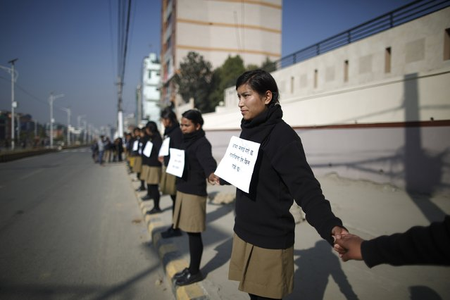 Students hold hands to form a human chain during a demonstration demanding for the right for Nepali mothers to pass on citizenship to their children, as a new constitution is drafted in Kathmandu December 24, 2014. The new assembly was elected to write a constitution after the abolition of the 240-year-old feudal monarchy that the Maoists fought against. (Photo by Navesh Chitrakar/Reuters)