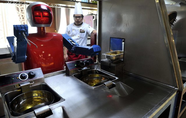 A cook stands behind a robot as it process food at the kitchen of a restaurant in Hefei, Anhui province, December 26, 2014. (Photo by Reuters/Stringer)