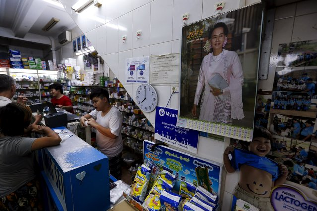 People shop in a drugstore with a calendar with a picture of Myanmar opposition leader Aung San Suu Kyi, in Yangon November 6, 2015. (Photo by Jorge Silva/Reuters)