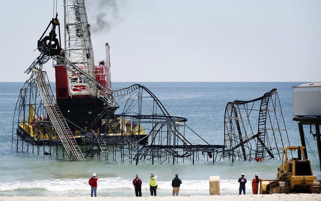 A barge moves into position as workers prepare to remove the Star Jet rollercoaster, on May 14, 2013, that has been in the ocean for six months after the Casino Pier it was built on collapsed when superstorm Sandy hit Seaside Heights, New Jersey. (Photo by Lucas Jackson/Reuters)