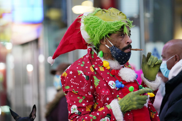 A man dressed in Christmas garb smokes a hand-rolled cigarette, Thursday, December 24, 2020, in Times Square on Christmas Eve in New York. (Photo by Kathy Willens/AP Photo)