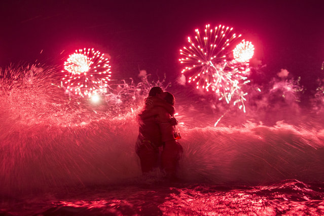 A wave crashes on two girls hugging as they usher in the new year, while fireworks explode over Copacabana beach, during New Year celebrations in Rio de Janeiro, Brazil, Thursday, January 1, 2015. (Photo by Felipe Dana/AP Photo)