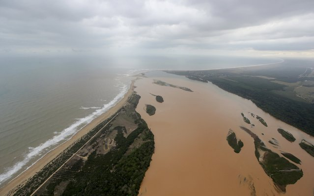 An aerial view of the mouth of Rio Doce (Doce River), which was flooded with mud after a dam owned by Vale SA and BHP Billiton Ltd burst, is seen as the river joins the sea on the coast of Espirito Santo, in Regencia Village, Brazil, November 21, 2015. (Photo by Ricardo Moraes/Reuters)