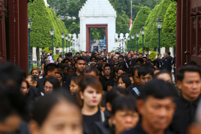 Mourners walk in line into the Throne Hall at the Grand Palace for the first time to pay respects to the body of Thailand's late King Bhumibol Adulyadej that is kept in a golden urn in Bangkok, Thailand, October 29, 2016. (Photo by Athit Perawongmetha/Reuters)