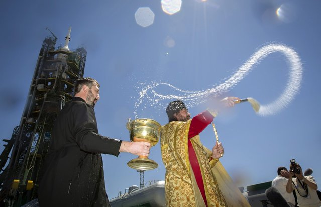 An Orthodox priest (C) conducts a blessing service in front of the Soyuz TMA-09M spacecraft on the launch pad at Baikonur cosmodrome May 27, 2013. Soyuz with U.S. astronaut Karen Nyber, Italian astronaut Luca Parmitano and Russian cosmonaut Fyodor Yurchikhin is due to travel to the International Space Station on May 29. (Photo by Shamil Zhumatov/Reuters)