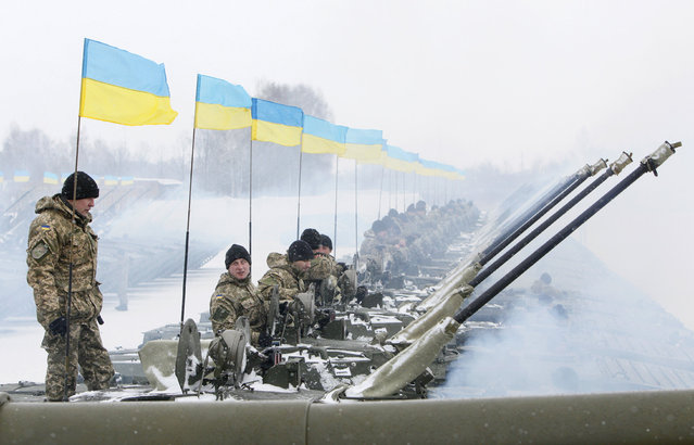 Ukrainian servicemen sit atop armoured personnel carriers (APC) during a ceremony to hand over weapons, military equipment and aircrafts to the army at a firing range outside Zhytomyr January 5, 2015. (Photo by Valentyn Ogirenko/Reuters)