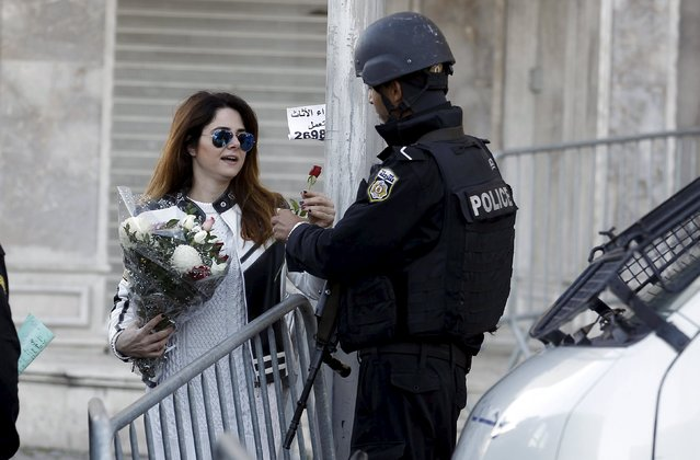 Tunisian woman gives flowers to a policeman in Tunis, Tunisia November 25, 2015. Tunisian security officials said on Wednesday a suicide bomber carried out the attack on a presidential guard bus, killing at least 13 and forcing the government to impose a nationwide state of emergency. (Photo by Zoubeir Souissi/Reuters)