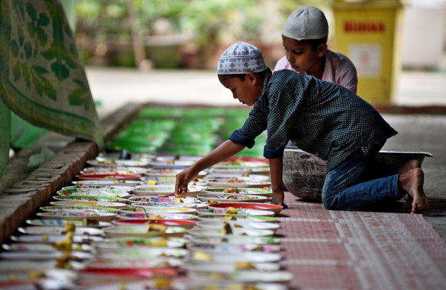 Muslim children arrange Iftar (breaking fast) meals inside a mosque during the holy fasting month of Ramadan, in Guwahati, India May 23, 2018. (Photo by Anuwar Hazarika/Reuters)