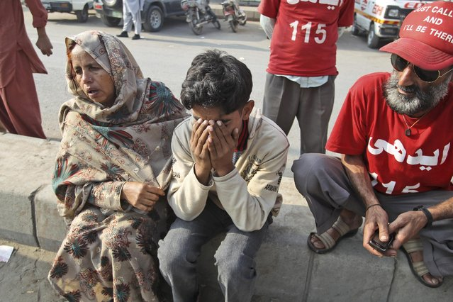 Relatives of a bus accident victim mourn his death outside a hospital in Karachi, Pakistan, Sunday, January 11, 2015. A bus was destroyed after colliding with an oil tanker on a highway about 50 kilometers (31 miles) outside of Karachi Sunday, killing more than 50 people. (Photo by Fareed Khan/AP Photo)