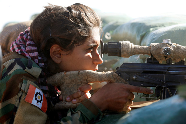 An Iranian-Kurdish female fighter aims with her weapon during a battle with Islamic State militants in Bashiqa, near Mosul, Iraq on November 3, 2016. (Photo by Ahmed Jadallah/Reuters)