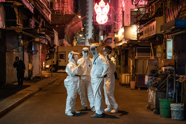 Government workers wearing personal protective equipment on a street in the locked-down part of the Jordon district on January 24, 2021 in Hong Kong, China. Hong Kong government locked-down tens of thousand of residents to contain a worsening outbreak of the coronavirus. Residents tested negative for Covid-19 can now leave and re-enter the area and the restriction is expected to lift by midnight. (Photo by Anthony Kwan/Getty Images)