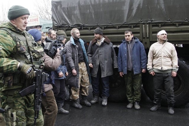 Prisoners of war (POWs), representing Ukrainian armed forces and escorted by members of the armed forces of the  separatist self-proclaimed Donetsk People's Republic, line up as they visit a site near the public transport stop, where civilians were earlier killed on Thursday, in Donetsk, January 22, 2015. (Photo by Alexander Ermochenko/Reuters)