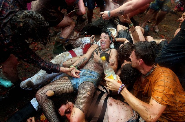 People take part in a tomato fight at the Common at the Glastonbury Festival of Contemporary Performing Arts site at Worthy Farm, near Glastonbury, England, on June 30, 2013. The festival, which started in 1970 when several hundred hippies paid 1 GBP to watch Marc Bolan, now attracts more than 175,000 people over five days. (Photo by Matt Cardy/Getty Images)