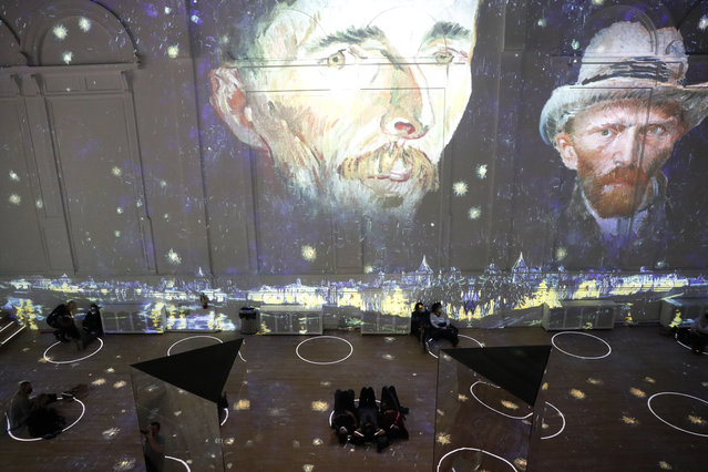 """Patrons socially distance as they look at the moving images cast on the walls, floors and reflecting mirrors during a virtual display titled """"Immersive Van Gogh"""" on Thursday, February 18, 2021, at the Lighthouse ArtSpace, in Chicago. (Photo by Shafkat Anowar/AP Photo)"""