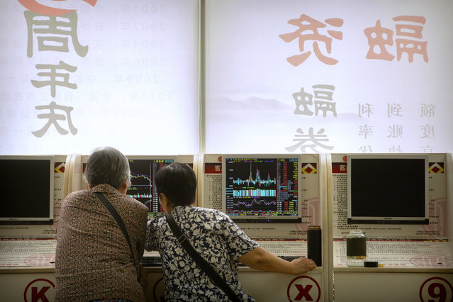 Chinese investors use computer terminals as they monitor stock prices at a brokerage house in Beijing, Friday, June 22, 2018. Asian stocks fell Friday following Wall Street losses overnight as investors were still wary over trade disputes between China and the U.S. as well as between the U.S. and Europe that could hurt corporate profit and jobs. (Photo by Mark Schiefelbein/AP Photo)