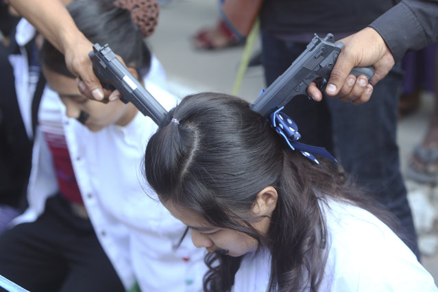 A woman depicts the plight of a civil servant being forced to work at gunpoint by the military junta during an anti-coup rally in Mandalay, Myanmar, Monday, February 22, 2021. (Photo by AP Photo/Stringer)
