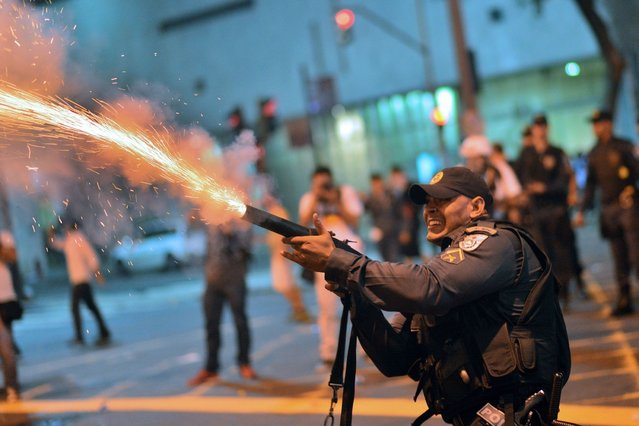 A riot police officer fires tear gas at violent demonstrators after clashes erupted following a march by Brazilian workers in Rio de Janeiro, on July 12, 2013. (Photo by Christophe Simon/AFP Photo)
