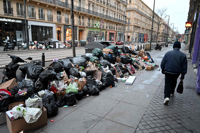 A pedestrian walks past an important stack of rubbish in the second district of Marseille, southern France, on December 28, 2020 as the company Polyceo, in charge of trash collection, is on strike since December 17, 2020. For nearly a week, some 200 employees of the company Polyceo, responsible for garbage collection and cleanliness in the 2nd, 15th and 16th arrondissements of Marseille have been on strike. More than 550 tonnes of waste were not collected in these areas, according to the Aix-Marseille-Provence Metropolis. (Photo by Nicolas Tucat/AFP Photo)