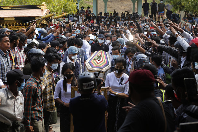 The casket containing the body of Mya Thwet Thwet Khine is carried through the crowds towards the cemetery in Naypyitaw, Myanmar, Sunday, February 21, 2021. Mya Thwet Thwet Khine was the first confirmed death among the many thousands who have taken to the streets to protest the Feb. 1 coup that toppled the elected government of Aung San Suu Kyi. (Photo by AP Photo/Stringer)
