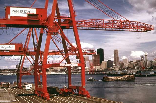 Port of Seattle freight handling equipment and city skyline, an industrial waste barge under tow to landfill on the Snohomish River estuary. (Photo by Doug Wilson/NARA via The Atlantic)
