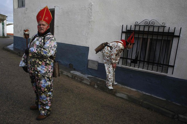 """Believers take a break from parading around town during the """"Endiablada"""" festival in Almonacid del Marquesado, in central Spain February 3, 2015. (Photo by Susana Vera/Reuters)"""