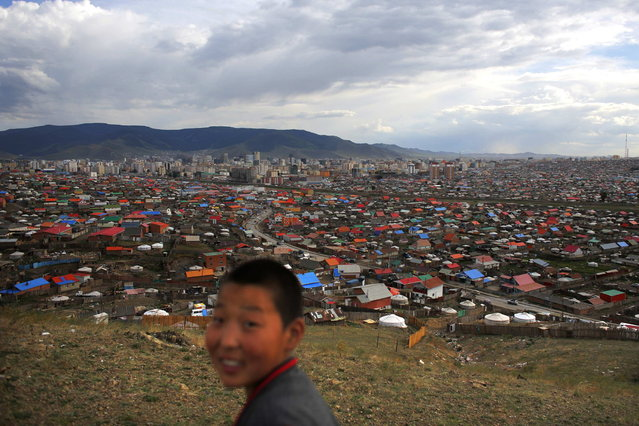 A boy walks at an area known as a ger district, where some residents live in traditional Mongolian tents, in Ulan Bator June 22, 2013. Approximately 60 percent of the population of Ulan Bator live in settlements known as ger districts and in many cases residents have limited access to basic services such as water and sanitation. According to a 2010 National Population Center census, every year between thirty and forty thousand people migrate from the countryside to the capital Ulan Bator. Ger districts in the city have been expanding rapidly in recent years. Mongolia is the world's least densely populated country, with 2.8 million people spread across an area around three times the size of France. (Photo by Carlos Barria/Reuters)