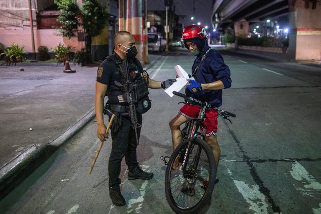 An armed police officer checks the documents of a cyclist at a checkpoint placed to implement a curfew in the country's capital amid rising coronavirus disease (COVID-19) cases, in Caloocan City, Metro Manila, Philippines, March 16, 2021. (Photo by Eloisa Lopez/Reuters)