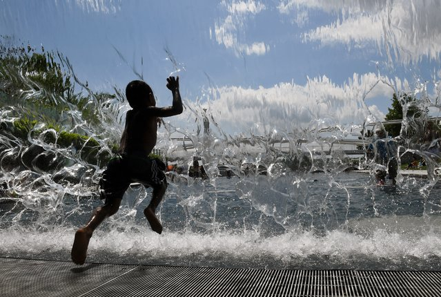 Aman Makonnen, 4, seeks relief from the heat as he jumps through a waterfall feature at the Yards Park in Washington, USA on May 20, 2018. (Photo by Matt McClain/The Washington Post)